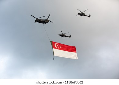 Singapore - Jun 23, 2018: Apache helicopter flying a giant Singapore flag over Marina Bay as part of Singapore National Day Parade (NDP) rehearsals.