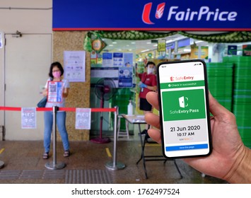 Singapore Jun21 2020 Show of SafeEntry (digital contact tracing app) on phone at NTUC Fairprice supermarket. Woman scanning entry code in the background. Circuit breaker; coronavirus outbreak; Phase 2