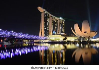Singapore, Singapore - June 03, 2016: Night view of the pedestrian Helix Bridge, a structure of glass and stainless steel leading to the Marina Bay Sands Hotel.