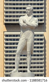 singapore, singapore - june 09, 2007: statue of sir thomas stamford raffles the founder of the city state at singapore river landing place, background: calculator building of ocbc bank  in cbd
