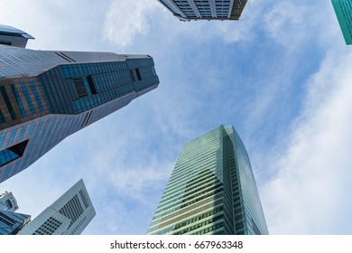 Singapore - June 17, 2017: Bottom view of modern skyscrapers in business district area against blue sky, Skyscraper Building Looking Up Blue Sky and Clouds