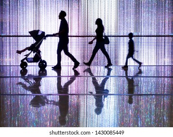 Singapore, June 21 2019; Silhouette of four family's member walking in a mall with digital light canvas in background