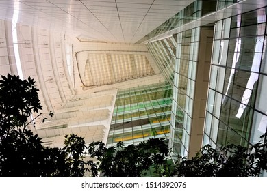 Singapore - June 22 2019: Futuristic abstract ceiling and glass wall of modern National Library Singapore framed by trees with strong architectural detail in vertical view