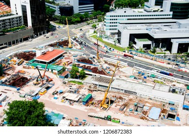 SINGAPORE - JUNE 23, 2018: an aerial view of the metro station under construction in the city with many cars running on the road next to it