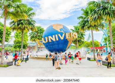 SINGAPORE - JUNE 25: Tourists and theme park visitors taking pictures of the large rotating globe fountain in front of Universal Studios on JUNE 25, 2014 in Sentosa island, Singapore