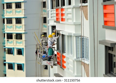 SINGAPORE - JUNE 25: Workers painting the exterior walls on June 25, 2015 in public housing block. About 90% of resident households owning their HDB flat in Singapore.