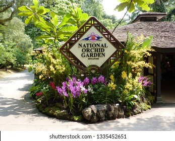 Singapore - June 30, 2010 - the entrance to the National Orchid Garden within Singapore Botanic Gardens, with a sign surrounded by red, yellow and pink vanda orchids and tropical foliage plants