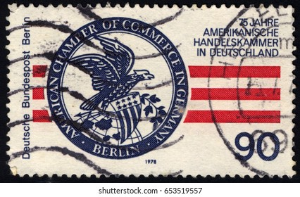 SINGAPORE – JUNE 5, 2017: A stamp printed in Germany ( Berlin ) shows emblem of the American Chamber of Commerce, 75 years american chamber of commerce in Germany (ACC), circa 1978