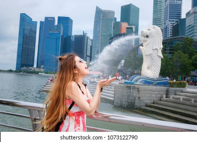 SINGAPORE - JURY 6, 2017 : Merlion statue fountain with asian tourist girl in Merlion park at  year 2017. Merlion is one of the most famous locate in Singapore