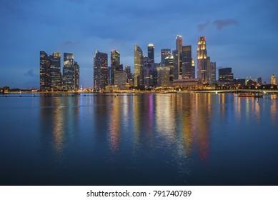 Singapore landmark city skyline at the Marina bay during sunset blue hour dusk with reflection.