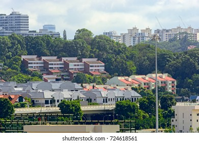 SINGAPORE, MALAYSIA - Jan 01, 2017: Low-rise apartment residential buildings behind of Port of Singapore container cargo terminal, run by PSA, one of the busiest shipping terminals in the world.