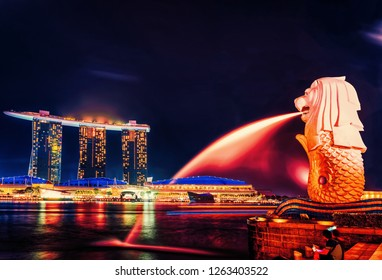 Singapore, Singapore - March 1, 2016: Merlion statue at Merlion Park at Marina Bay in Singapore, at night. Marina Bay Sands hotel building on the background. Illuminated with light at night
