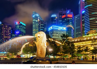Singapore, Singapore - March 1, 2016: Merlion statue spraying the water from its mouth at Merlion Park in Downtown Core of Singapore at Marina Bay at night. Skyline with Skyscrapers on background