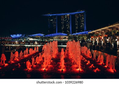 SINGAPORE -  MARCH 1, 2018: Singapore Night. Marina Bay Sands and red fountain.