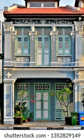 Singapore - March 11th 2019: Front view of traditional Singapore Straits Chinese or Peranakan shop house entrance and 1st floor with strong architectural detail and colours in historic Joo Chiat