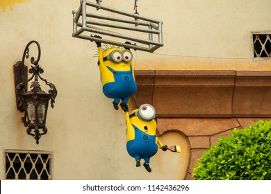 Singapore - March 2, 2018: Minions a famous yellow cartoon character hanging from metal cage with paint brush in hand decorate at Minion Mart shop in Universal Studios Singapore.
