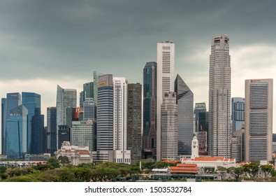 Singapore - March 20, 2019: Line of financial district skyscrapers from DBS to OCBC bank buildings under dark gray cloudscape. Victoria theatre and Cricket Club in front with green foliage and red roo