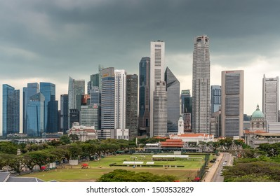 Singapore - March 20, 2019: Line of financial district skyscrapers from bay to Singtel building under dark gray cloudscape. Victoria theatre, National Gallery dome and Cricket Club in front.