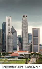 Singapore - March 20, 2019: Partial portrait of financial district skyscrapers from Capitaland to OCBC Bank buildings under dark gray cloudscape. Victoria theatres clock tower and Cricket Club in fron