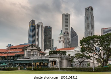 Singapore - March 20, 2019: Towers of Financial district behind the historic buildings of Cricket Club and Victoria Theatres clock tower. Green lawn and foliage. Red roofs and cloudscape.