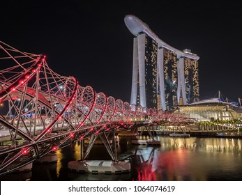 Singapore - MARCH, 2018: Marina Bay Sands, Helix bridge and Artscience museum cityscape at night. Futuristic architecture and modern design.