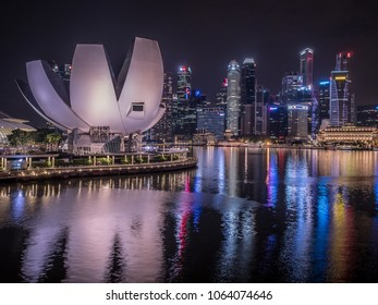 Singapore - MARCH, 2018: Night panorama of Singapore. Artscience museum and skyscrapers on the background. Reflections on the water.