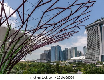 Singapore - March 22, 2019: Gardens by the Bay, Supertree Grove. Marina Bay Sands hotel and casino and Financial Dsitrict under blue sky partly hidden and fronted by branches of supertree.