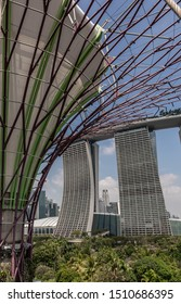 Singapore - March 22, 2019: Gardens by the Bay, Supertree Grove. Marina Bay Sands hotel and casino under blue sky partly hidden and fronted by branches of supertree. Green of park.
