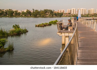 SINGAPORE - MARCH 23, 2014: Jurong Lake Park walkway with apartments in the background