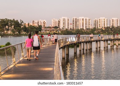 SINGAPORE - MARCH 23, 2014: People strolling along the new pedestrian walkway next to Jurong Lake