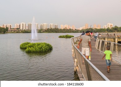 SINGAPORE - MARCH 23, 2014: People strolling along the Jurong Lake Park walkway