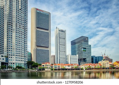 Singapore - March 24, 2018: 2-3 floor old shop-houses on the Boat Quay contrasted the highest skyscrapers of UOB Plaza and OCBC Centre of 280 and 197 m respectively