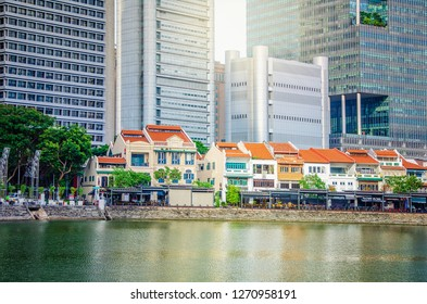 Singapore - March 24, 2018: A view at Boat Quay on the South bank of the Singapore river. Two-and three-story restored shop-houses in that area stay in front of tall skyscrapers.