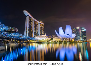 SINGAPORE - MARCH 24, 2019: The Helix Bridge, the Marina Bay Sands hotel and the ArtScience Museum at night.
