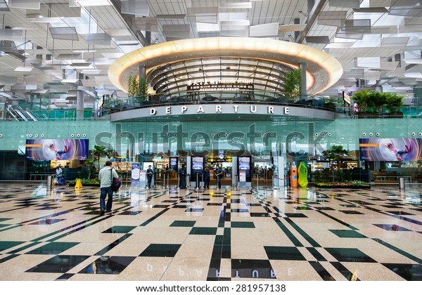 SINGAPORE - MARCH 24 : Travelers walk about Singapore Changi Airport's departure hall Mar. 24, 2015. With three passenger terminals, it is one of the largest transportation hubs in Asia.