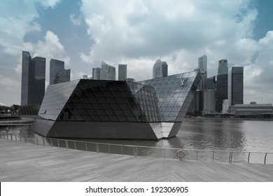 "SINGAPORE - MARCH 27, 2014 : Louis Vuitton at Marina Bay Sands. It is located in a floating ""Crystal Pavilion"" designed by Safdie Architects, an asymmetric building with irregularly angled facades."