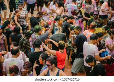 Singapore, March 3, 2018: Holi celebration in Sentosa, Singapore. A throng of Indians sing and dance in a pool of water to music. They smear color and splash water on one another.
