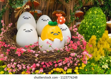 Singapore - March 4, 2018: Festive Easter decoration at Changi International Airport, colorful lighting garden of lazy egg toy party, yellow lazy egg cartoon out of white cracked eggshell in bird nest