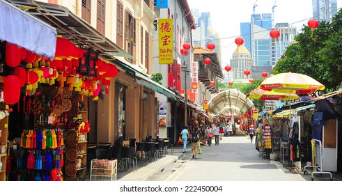 SINGAPORE - MARCH 5, 2013: Shoppers walking on Chinatown street in Singapore. The city state's ethnic Chinese began settling in Chinatown circa 1820s.