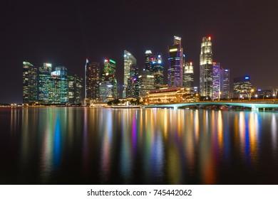 Singapore Marina Bay Cityscape. Skyscraper along Marina Bay at night time. Beautiful light reflection on the water.
