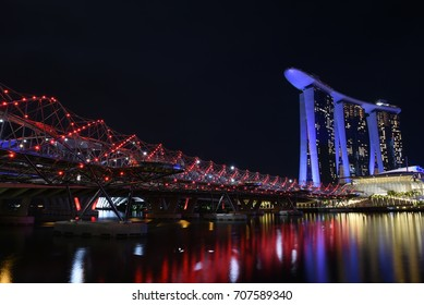 Singapore, Singapore - May 11, 2017: Night view of the pedestrian Helix Bridge, a structure of glass and stainless steel leading to the Marina Bay Sands Hotel.