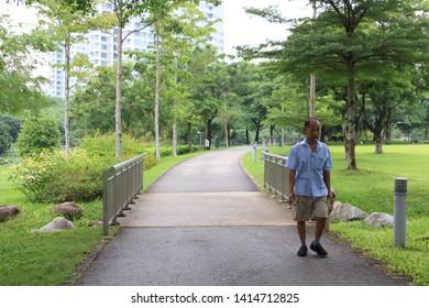 Singapore, Singapore - May 11: Elderly man taking a walk in the morning at Bishan Ang Mo Kio Park.