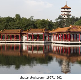 SINGAPORE - MAY 15, 2014: Chinese design covered walkway beside lake with pagoda in the background