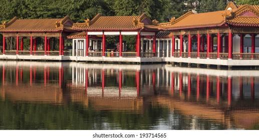 SINGAPORE - MAY 15, 2014: Chinese design covered walkway beside lake