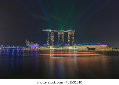 SINGAPORE - MAY 15: Singapore's Merlion statue watches over laser lights emanating from the Marina Bay Sands Hotel May 15, 2016. The nightly display lights up Marina Bay in a spectacular display.