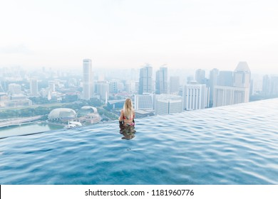 Singapore, May 17, 2018. Girl looks to Singapore cityline from infinity pool.