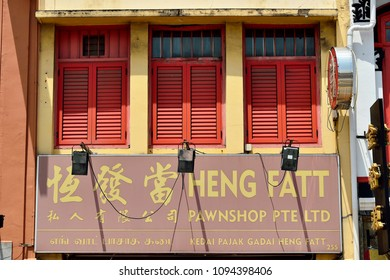 Singapore - May 17th 2018: Front view of Heng Fatt Pawnshop with antique red wooden shutters and signage in historic Chinatown