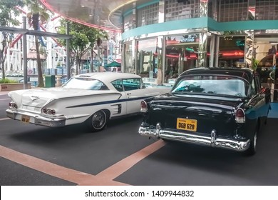 Singapore - May 25, 2019: Old vintage Chevrolet white parked on the street near other black retro car. Back side view