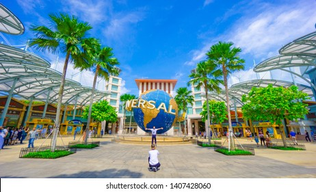 Singapore - May 25, 2019: Tourist taking photos with Universal Studios globe in Sentosa island during cloudy day. Universal Studios Singapore is Southeast Asia's first Hollywood movie theme park.