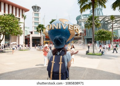 SINGAPORE - MAY 28 2018 : Tourists and theme park visitors taking pictures of the large rotating globe fountain in front of Universal Studios on MAY 28, 2018 in Sentosa island, Singapore
